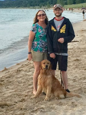 Beth Bascom, her son, Tony Stack, and their dog, Ozzie, on vacation in July at Lake Michigan beach in Pentwater. Bascom relied on Doggie in the Window day care in Berkley to take care of him as she worked long hours as an emergency room physician during the pandemic.