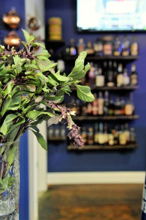 A glass of fresh Thai basil and more than 100 bottles of Bourbon are waiting to be added to the cocktails at Jennings Street Public House in Newburgh on Thursday, Oct. 22, 2020.