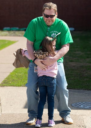 CazeElementary School behavioral specialist Jeff Crowe gives Carleigh Eaden, 5, a hug after he spotted her and her sister, Raelynn Chase Eaden, 6, at the school Tuesday morning, March 17, 2020. The Evansville Vanderburgh School Corporation was closed due to the coronavirus pandemic and had started offering meals that day. Crowe, also a pastor at Cup Creek General Baptist Church in Velpen, Ind., died after a long battle with COVID-19 Monday afternoon, Oct. 26, 2020.
