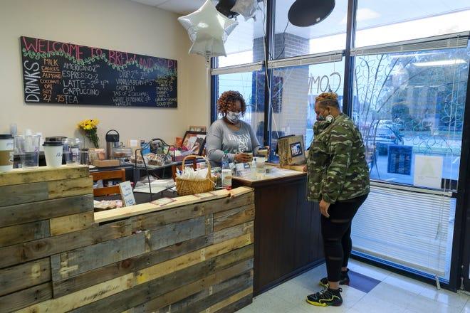 Brew & Sip Coffee owner Latoya Cook-Bradley waits on Marisa Hall on Monday, October 26, 2020.