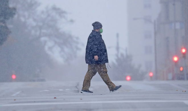 A pedestrian crosses East Wells Street on North Jackson Street as the snow falls in Milwaukee on Monday, Oct. 26, 2020.  -  Photo by Mike De Sisti / Milwaukee Journal Sentinel