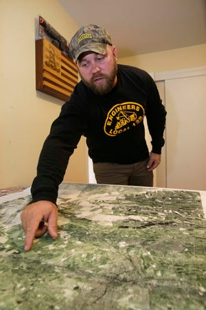 Leroy Miller looks at a map of the Karshi-Khanabad Air Base in Uzbekistan, known as K2. Miller arrived in K2 to train for the invasion of Afghanistan. He returned to K2 after several months in Afghanistan and didn't know that the former Soviet air base was filled with chemical weapons, asbestos, radioactive processed uranium and other toxins.