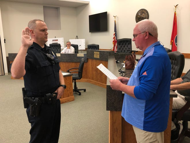 Dickson Mayor Don L. Weiss Jr. (right) administers the peace officer's oath to Dickson Police Department Officer Andrew Gilbert (left).
