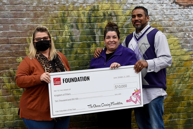 Malissa Moran, the Newark Wellness Leader for Owens Corning, gives a check for $10,000 to Darcey and Jay McCampbell, co-founders of Newark-based Kingdom Pillars Strong Tower. The local charity works with young women aging out of the foster care system, and those who have been trafficked between the ages of 18-25.