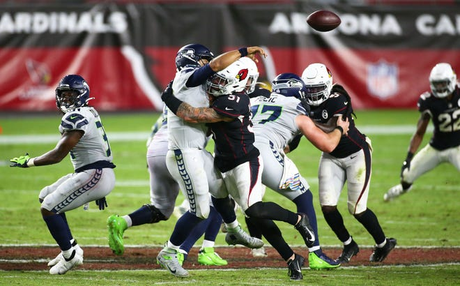 Oct 25, 2020; Glendale, AZ, USA; Arizona Cardinals linebacker Tanner Vallejo (51) tackles Seattle Seahawks quarterback Russell Wilson (3) in overtime during a game at State Farm Stadium. Mandatory Credit: Rob Schumacher/The Arizona Republic via USA TODAY NETWORK