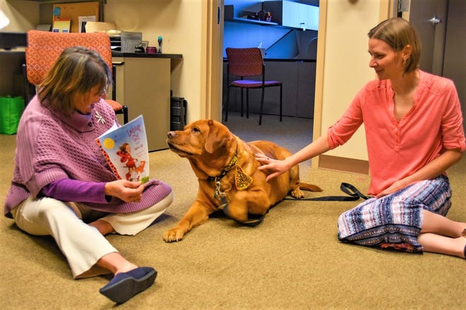 Alison Lanza Falls, left, reads an Imagination Library book to her dog, Yogi, in the United Way in Ottawa County office while April Schalk watches. The two women were instrumental in bringing the Imagination Library to program to Ottawa County.