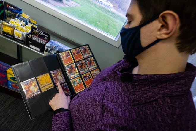 Gage Badgerow flips through a binder of Pokemon cards Friday, Oct. 23, 2020, in one of the game rooms at Great Lakes Gaming's new location.