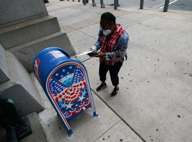 A voter prepares to drop off a ballot at a drop box outside Philadelphia City Hall on May 28, 2020. In a tie vote Monday the Supreme Court rejected a Pennsylvania GOP appeal regarding mail ballots. (Yong Kim/The Philadelphia Inquirer/TNS)