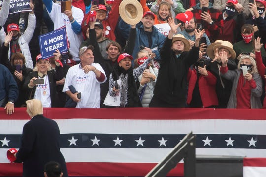 President Donald Trump tosses MAGA caps to the crowd at the conclusion of a campaign rally at Lancaster Airport in Lititz, Pa., on Monday, October 26, 2020.