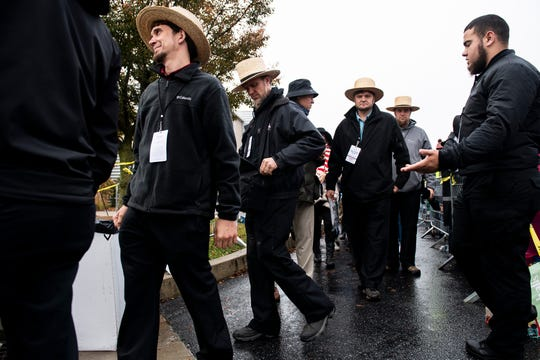 Men dressed in Amish garb wait in line before entering a Trump campaign rally in Lititz, Pa., Monday.