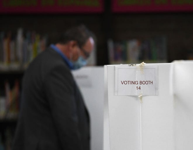 A voter casts his vote at the library in dowtown Reno on Oct. 26, 2020