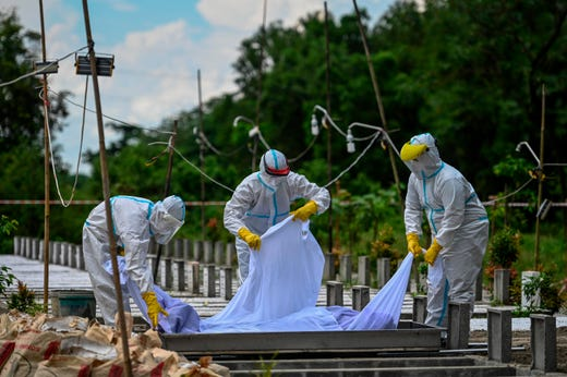 Volunteers wearing personal protective equipment (PPE) suits bury the body of a person suspected of dying from the COVID-19 coronavirus at a cemetery, in Yangon on Oct. 26, 2020.