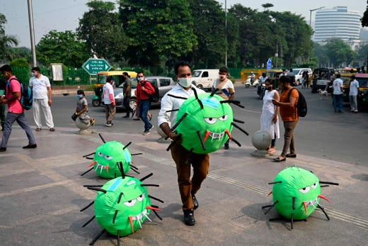 An officer from the district magistrate office holds a COVID-19 coronavirus-themed mascot in a market area during an awareness campaign against coronavirus and rising air pollution levels in New Delhi on Oct. 26, 2020.