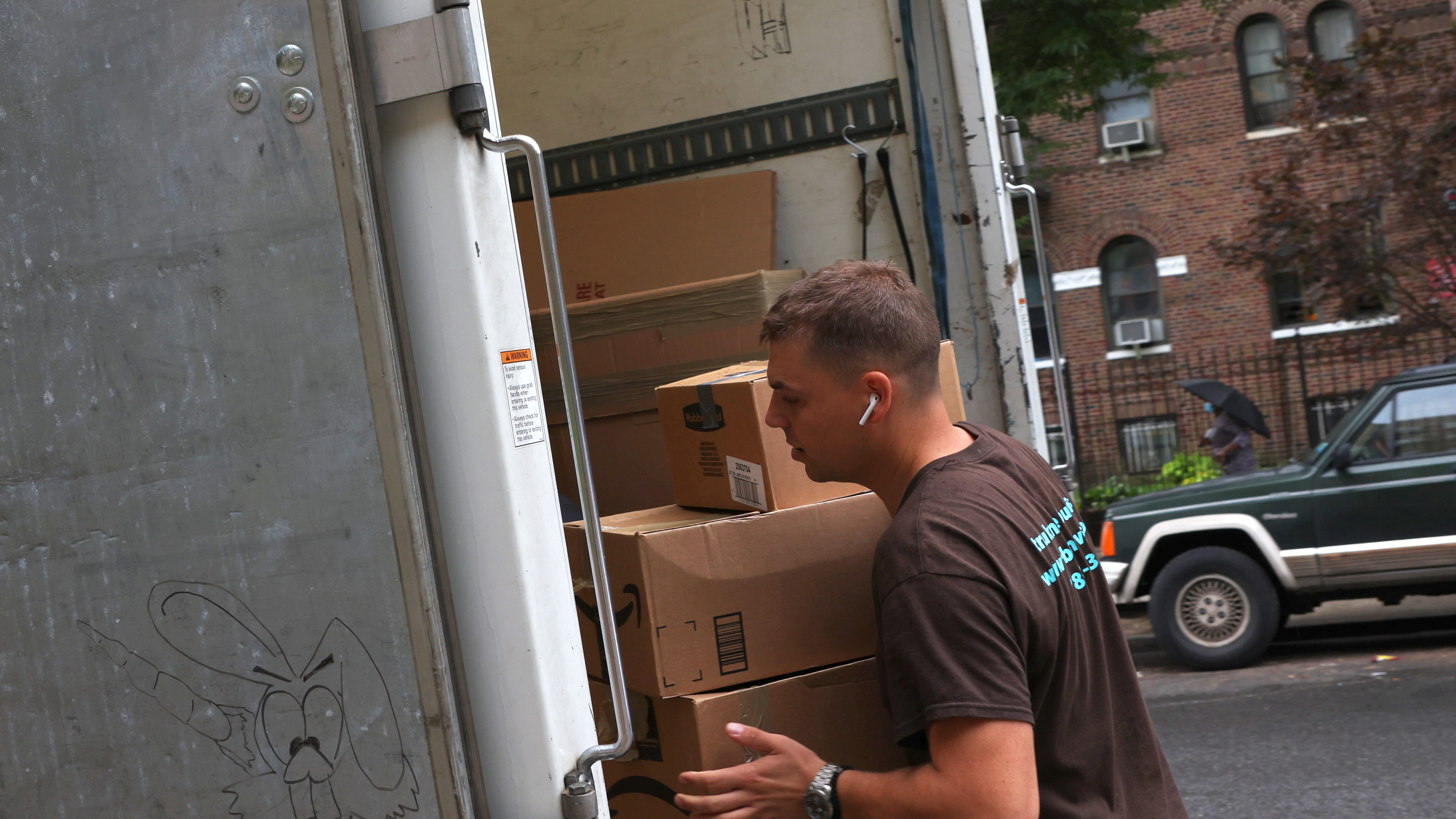 Dusan B., a mover with Rabbit Movers, places the belongings of a customer onto a moving truck on August 13 in New York City.