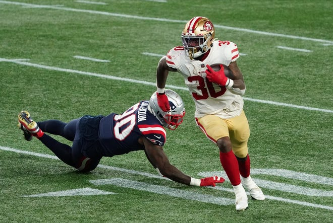 The 49ers' Jeff Wilson, who had 17 carries for 112 yards, eludes a tackle during Sunday's game against the Patriots, as New England continued to struggle against the run.