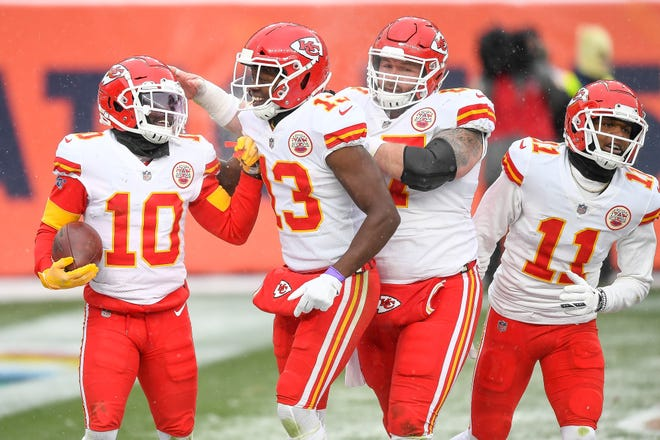 Tyreek Hill of the Kansas City Chiefs celebrates a fourth quarter touchdown with teammates Byron Pringle #13, Daniel Kilgore #67, and Demarcus Robinson #11 during a game against the Denver Broncos at Empower Field at Mile High on October 25, 2020 in Denver, Colorado.