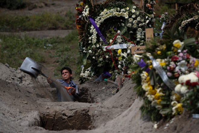 A cemetery worker digs a grave at the Valle de Chalco Municipal Cemetery on the outskirts of Mexico City on Sept. 24. The cemetery opened early in the coronavirus pandemic to accommodate the country's surge in deaths.