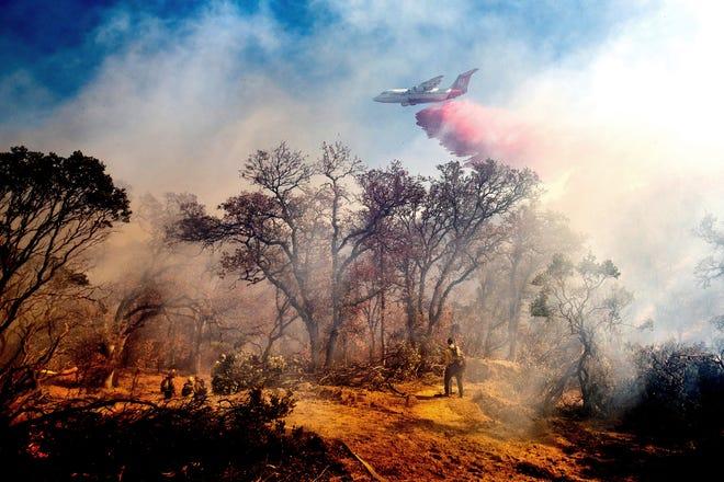 Un camión cisterna deja caer retardante en el incendio de Olinda en Anderson, California, el domingo 25 de octubre de 2020. El incendio fue uno de los cuatro incendios que ardían cerca de Redding que los bomberos se apresuraron a detener cuando los fuertes vientos azotaron el norte de California.  (Foto AP / Noah Berger)