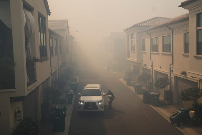 A man leaves his home during a mandatory fire evacuation as smoke from the Silverado Fire fills the air in Irvine, Calif.
