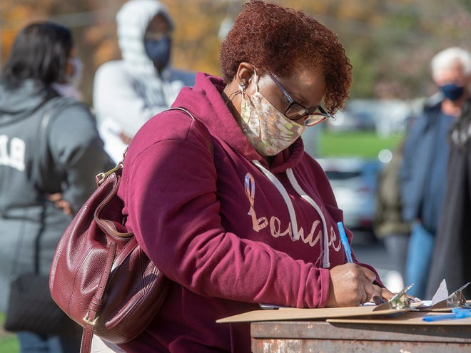 Felicia Hardrick, of Langhorne, fills out her mail in ballot, after waiting in line for hours, outside the Lower Bucks County Government Service Center in Levittown, on Tuesday, Oct. 27, 2020.