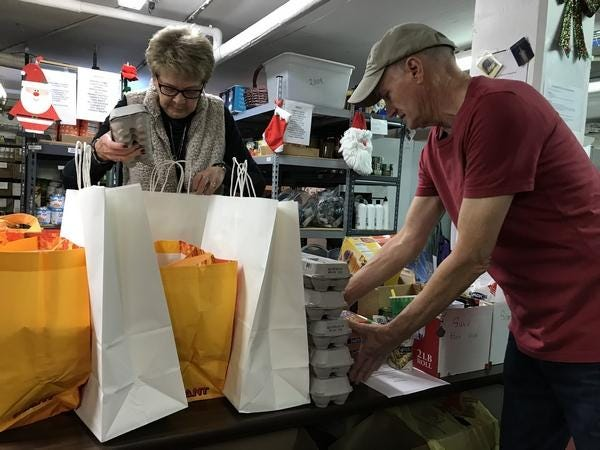 File - Barbara McCourt, of Langhorne, and Tim Rizzo, of Bristol Township, pack groceries for the needy in Tullytown in November 2019.