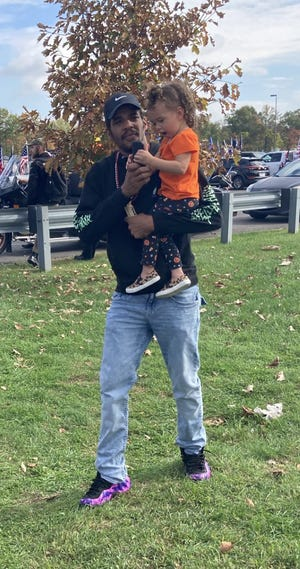 Jordan Vaughn with his daughter, Ainsley, 2, with Trump supporters at the Joe Biden rally in Bristol Township, Oct. 24, 2020.