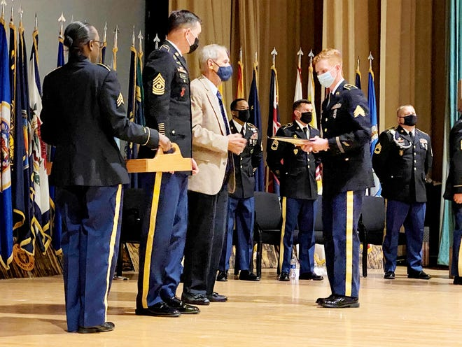 Sgt. Justis Balance, 204th Military Police Company, receives a copy of the Noncommissioned Officer's Creed and a certificate from retired Army Command Sgt. Maj. Edward M. Keuten and 519th Battalion Command Sgt. Maj. Michael P. McTernan during the NCO Induction Ceremony at Bayou Theater on Oct. 15.