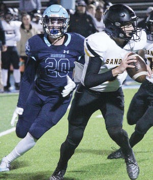 Bartlesville High's Rocky Shuman, left, pursues Sand Spring quarterback Ty Pennington during last year's game.