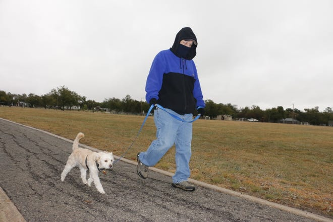 Tom Perkins of Brownwood walks with Teddy, a rescue dog who belongs to his mom, Janet Perkins, on a chilly, wet Tuesday morning in Coggin Park. With the temperature in the low 30s, Perkins said one lap was enough. Tuesday's temperature stayed in the 30s, with rain off and on. Wednesday's high is forecast at 51.