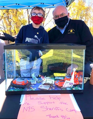 Yates County Sheriff Ron Spike personally thanked Colt Wicker, 7, of Altay, for his idea of collecting donations for the NY State Sheriffs' Summer Camp for Kids at the October Fall Festival in Dundee Oct. 17. For his efforts Sheriff Spike also made Colt a Jr. Deputy.