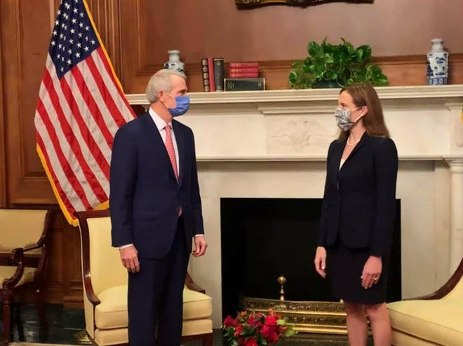 Ohio GOP Sen. Rob Portman meets last week with Judge Amy Coney Barrett, whom he voted to confirm Monday night as the newest U.S. Supreme Court justice. Now Democrats are raising money to defeat him in 2022.