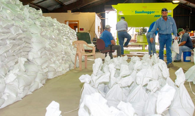 Assistant Supervisor Santo Lusco III hauls sandbags into piles of 25 bags on the shop floor of the Raceland Agricultural Center. Tuesday morning the crew had about 10-12,000 sandbags stacked and ready for residents preparing for Hurricane Zeta.