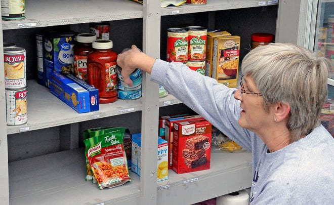 Cindy Mykrantz, a lay leader at Oak Chapel United Methodist Church, fills the shelves of the blessing box food pantry located in the parking lot of the church.