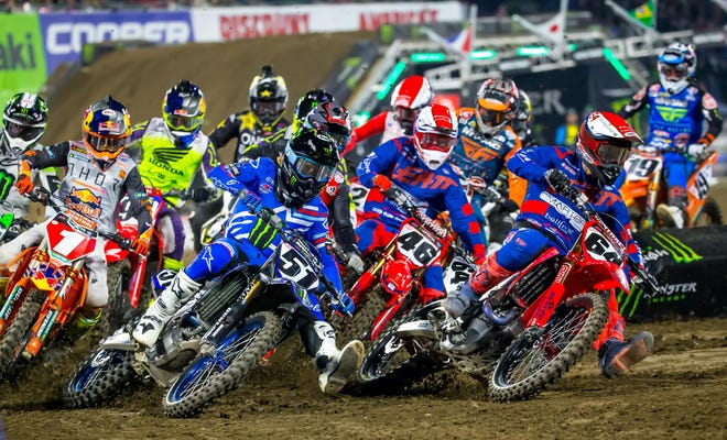 Supercross riders battle for position at the start of a 2020 race.