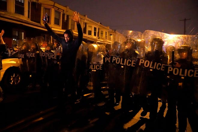Sharif Proctor lifts his hands in front of the police line during a protest in response to the police shooting of Walter Wallace Jr. on Monday in Philadelphia. Police officers fatally shot the 27-year-old Black man during a confrontation Monday afternoon in West Philadelphia that quickly raised tensions in the neighborhood. (Jessica Griffin/The Philadelphia Inquirer via AP)