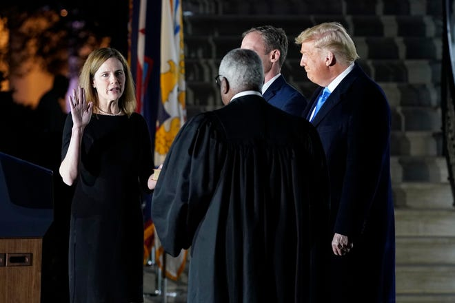 President Donald Trump watches as Supreme Court Justice Clarence Thomas administers the Constitutional Oath to Amy Coney Barrett on the South Lawn of the White House in Washington on Monday night after Barrett was confirmed by the Senate earlier in the evening. (AP Photo/Patrick Semansky)
