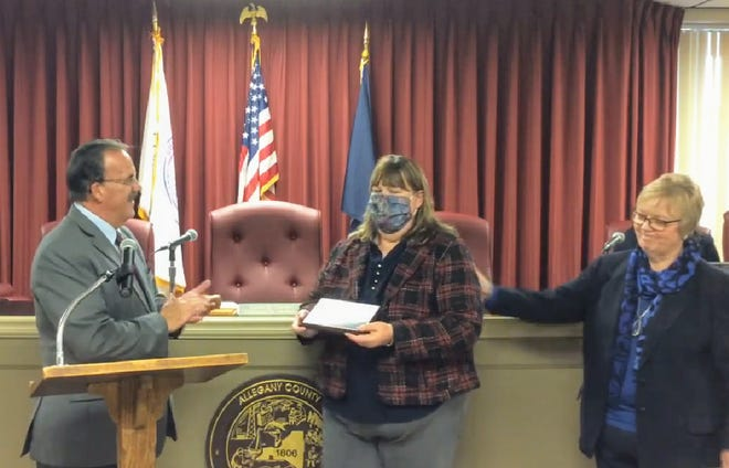 Allegany County Board of Legislators Chairman Curt Crandall, left, and Legislator Judy Hopkins present Public Health Director Lori Ballengee, center, with a plaque in appreciation of her service Monday. Ballengee is retiring after 30 years with the county.