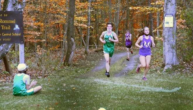 West Canada Valley's Catherine Christensen (right) and Herkimer's Peter Mosny exit the woods ahead of West Canada Valley's Louis Clarke during Wednesday's varsity race at West Canada Valley.