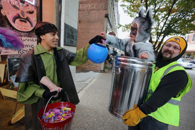 Isaac Holland, dressed as a pirate, hands candy to Phoenix Mitchell, 2, of Burlington, dressed as a raccoon in a garbage can, Oct. 27, 2017,  as he is held by his father, Michael, during the annual Downtown Trick-or-Treat in Burlington.