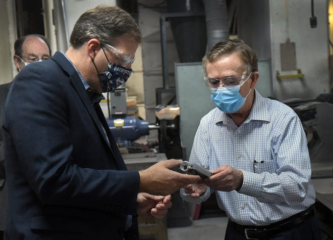 Gov. Chris Sununu, left, looks at a medical part explained by RP Abrasives owner Joe Shean on Tuesday in Rochester. Sununu received the endorsement of the NFIB NH Chapter.