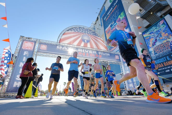 Runners cross the finish line of Saturday's 2020 Gate River Run. Over 12,300 runners completed the race, which will be capped at 8,000 participants for 2021.