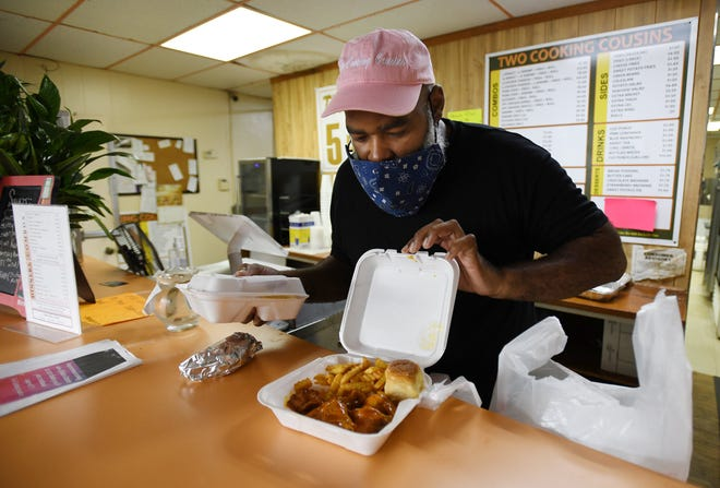 Owner Gary Nath checks on a customer's order before bagging it up at his Two Cooking Cousins restaurant on Tuesday. The takeout restaurant is located in Northwest Jacksonville at 1807 W. 45th St.