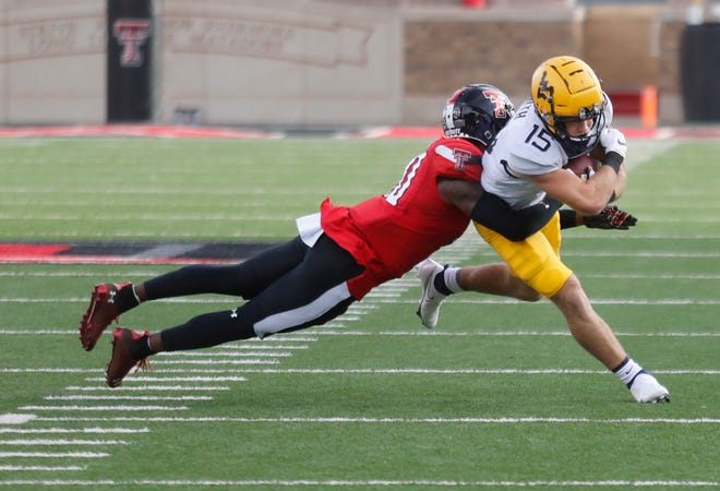 Texas Tech defensive back Cam White, left, tackles West Virginia receiver Reese Smith during the Red Raiders' 34-27 victory Saturday at Jones AT&T Stadium. Tech coach Matt Wells has made tackling drills a priority, and the Red Raiders' missed tackles have been less glaring this season.