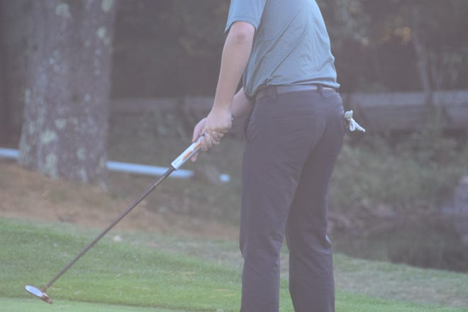 Wachusett varsity golfer Mitch Bullett lines up a shot.
