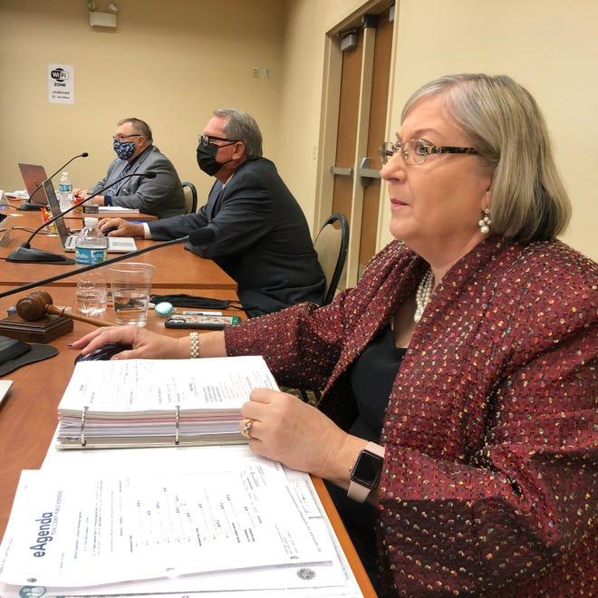 School Board Chairwoman Lori Cunningham, Vice-Chairman Lynn Wilson and Deputy Superintendent John Hill look over the agenda of the School Board meeting on Tuesday.