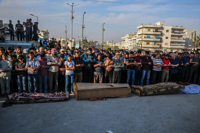 People attend funeral of fighters killed in an airstrike in the town of Idlib, Syria, on Monday. An airstrike on a rebel training camp in northwestern Syria on Monday killed dozens of Turkish-backed fighters and wounded nearly as many, in one of the heaviest blows to the opposition's strongest groups, a spokesman and a war monitor said.