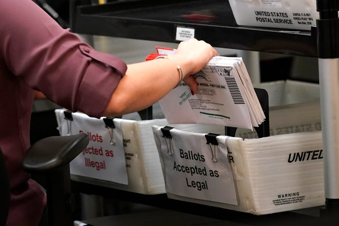 An election worker sorts vote-by-mail ballots at the Miami-Dade County Board of Elections on Monday in Doral.