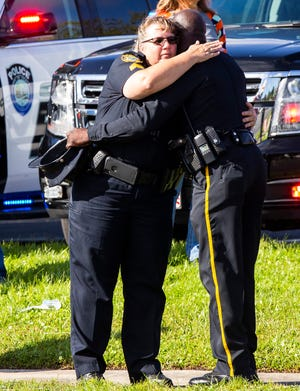Ocala Police Sgt. Melissa Buetti gets a hug from Williston Police Officer Mike Rolls on Tuesday. They were among those who gathered at the Ocala Police Department to watch as a hearse took the body of Ocala Police Chief Greg Graham to the Hiers-Baxley Funeral Home.