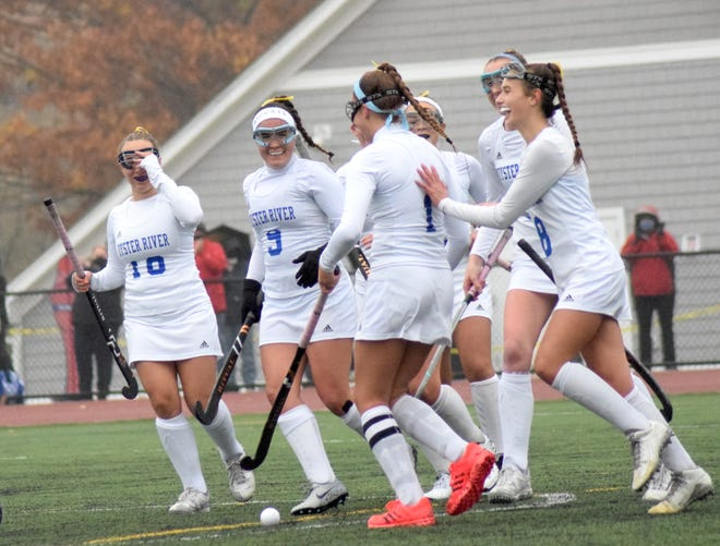 Oyster River field hockey players mob junior Ashley Harvey (1) after she scored on a penalty stroke during the second quarter on Monday. The Bobcats defeated Pelham, 2-1, to reach the Division II semifinals.