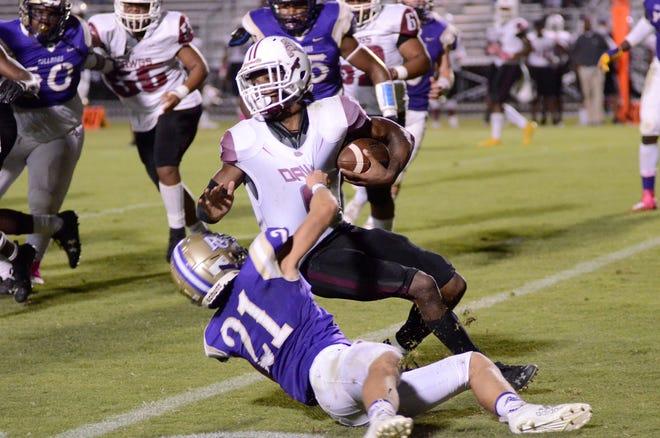Ascension Catholic's Brayden Duhon tackles White Castle quarterback Tahj Favorite.